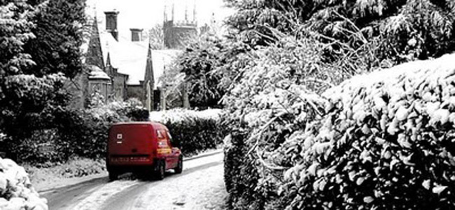 Snowy scene of Church Road Hilmarton with Post Office Van